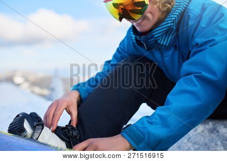 Snowboarder Straps In His Legs In Snowboard Boots In Modern Fast Flow Bindings With Straps. Rider At