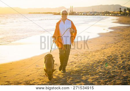Happy Attractive Senior Woman With Her German Shepard Dog Walking On The Beach At Autumn Sunset