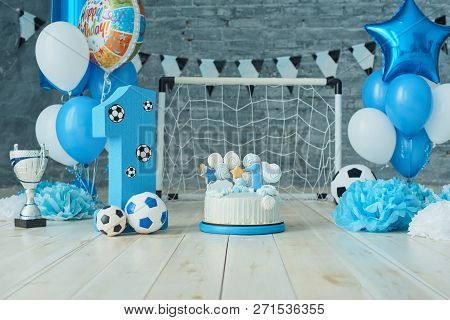 Festive Background Decoration For Birthday With Cake, Letters Saying One And Blue Balloons In Studio