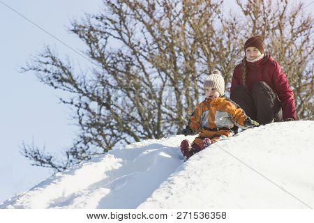 Mom And Son Moving Down A Snow Slide. Winter Day
