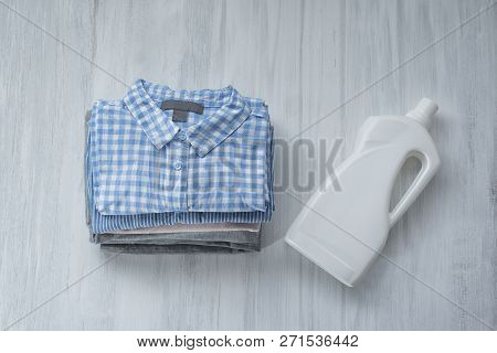 Stack Of Folded Shirts And Detergent Bottle. Top View