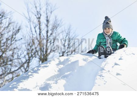 The Boy In Hat, Scarf And Green Jacket Slides Down From A Snow Slide On Back. Winter Day