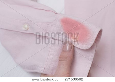 Sleeve Of A Pink Shirt With A Stain In Female Hand.