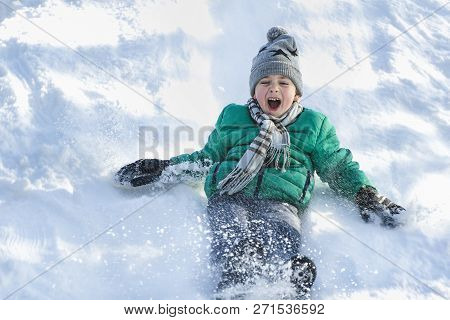 The Boy In Hat, Scarf And Green Jacket Slides Down From A Snow Slide On Back. Portrait. Close-up. Wi