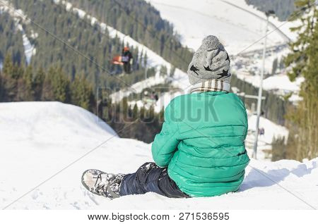 Boy Sits On A Snow-covered Hill On Background Of Cable Car, Pine Forest And Mountains. Ski Resort. W