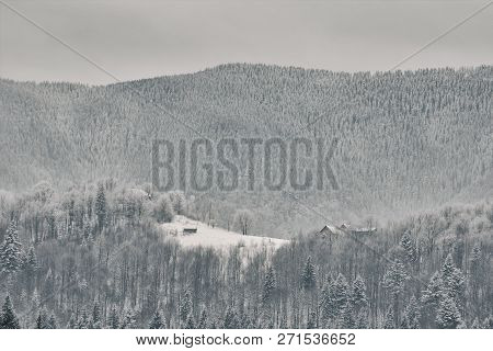 Snow-covered Mountain Slopes. Small House In The Distance