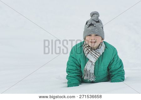 Boy In A Hat, Scarf And Green Jacket Is Lying In The Snow On His Elbows. Portrait. Close-up. Winter