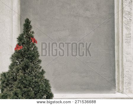 Christmas Tree With Red Bows On A Gray Wall Background, Copy Space.