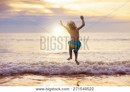 Child Playing On Ocean Beach. Kid At Sunset Sea.
