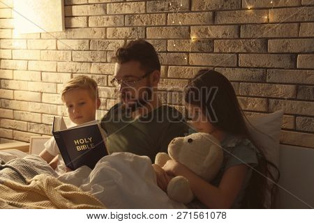 Father reading Bible to his little children in bed