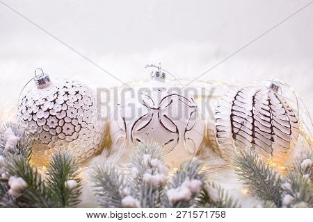 Three White Balls On White Fur Background. Decorative Christmas Composition. Selective Focus. Winter