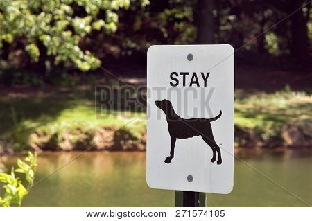 A black and white metal sign giving dog commands.
