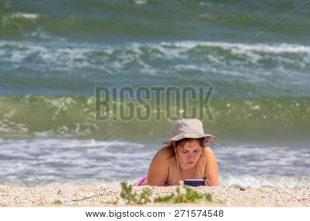 Young Woman In Hat Reading An Ebook Or Tablet On The Beach Lying On The Sand