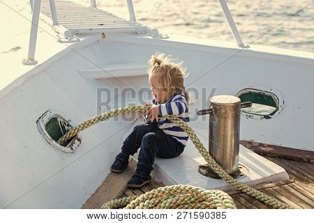 Boy Kid Playing With Rope On Yacht. Little Child Sitting And Berthing Rope On White Boat. Travel And