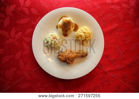 Chicken Dinner. Top down a Chicken Dinner. White plate. Red Table Cloth. Chicken Leg. Biscuit. Coleslaw. Mashed Potatoes and Gravy. Macaroni and Cheese. A meal fit for a King.
