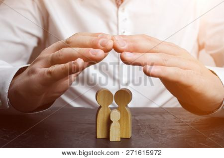 Insurance Agent Holds Hands Over Family. The Concept Of Insurance Of Family Life And Property. Famil