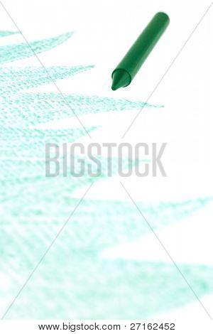 Green crayon with drawn grass close-up