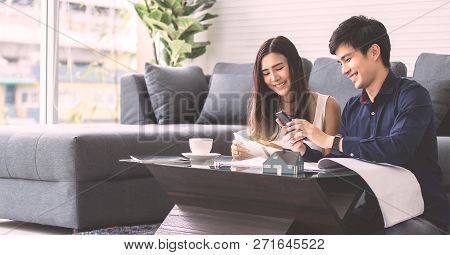 Asian Couple Smile Happily Is Planning To Build His Home In The Future. Choose From A Tablet In Hand