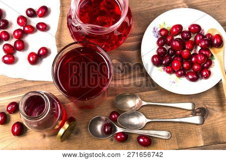 Organic Cranberries And Cranberry Juice With Cold Ice Cubes In A Glass On A Wooden Table