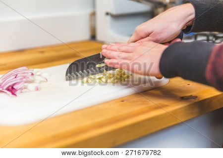 Caucasion Woman Wearing Long Sleeves Cuts Up Pieces Of Garlic On A Plastic Cutting Board. Sliced Red