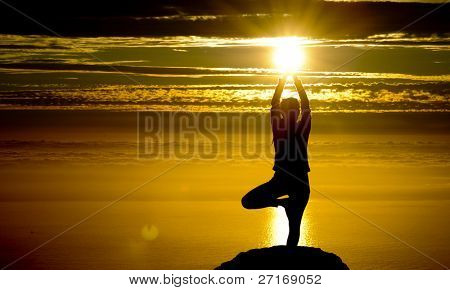 Girl does yoga at sunset on top of a mountain