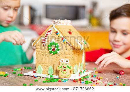 Family Build A Gingerbread House For Christmas. Kids Decorating The Gingerbread House