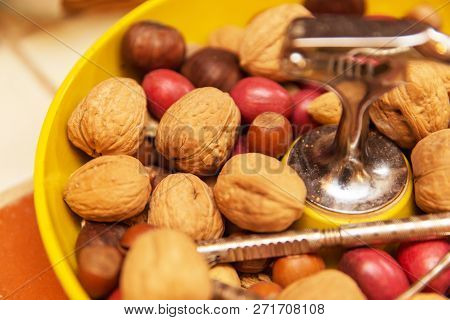 Walnuts And Chestnuts In A Bowl With Cracking Tools Or Utinsels.