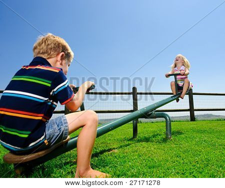 Kids playing at the see-saw in the playground