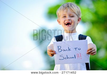 Young boy holds up handwritten sign