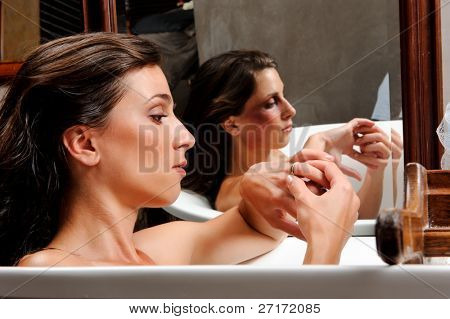 Woman relaxing in bathtub with mirror image of her with bruises on her face, a conceptual shoot of domestic abuse often hidden from public
