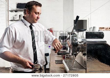 professional expert barista makes coffee with a machine