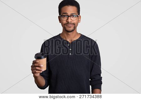 Horizontal Shot Of Serious Black Young Man Holds Takeaway Coffee, Wears Transparent Glasses, Has Bre