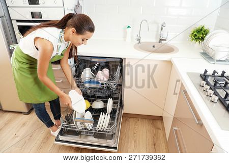 Beautiful young woman loading dishwasher in kitchen. Cleaning chores poster