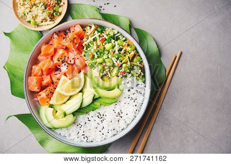 Tasty appetizing poke bowl served with salmon, avocado, rice, salad with edamame. Grey background. View from above with copy space. poster