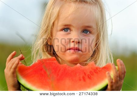 Young blonde girl wonders if she wants to continue eating this not so sweet watermelon