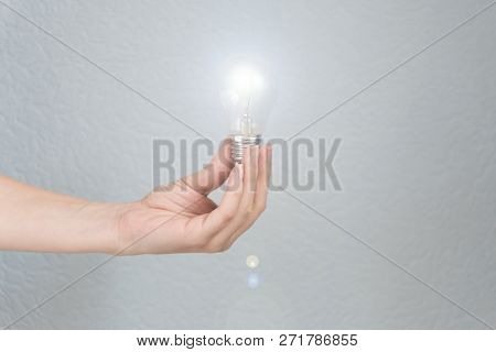 Woman Hand Holding Light Bulb. Idea And Busines Concept.