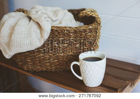 Cozy Winter Interior Details In White And Brown Tones. Basket With Knitted Sweater And Cup Of Coffee