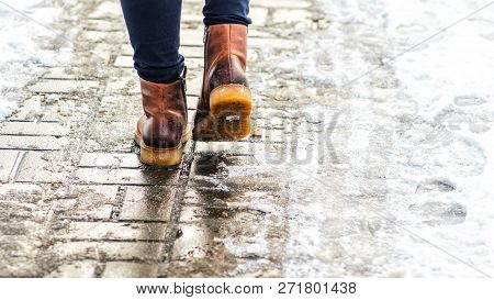 Walk On Wet Melted Ice Pavement. Back View On The Feet Of A Man Walking Along The Icy Pavement. Pair
