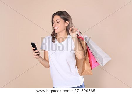 Cheerful Young Girl In Basic Clothes Using Mobile Phone While Holding Shopping Bags Isolated Over Be