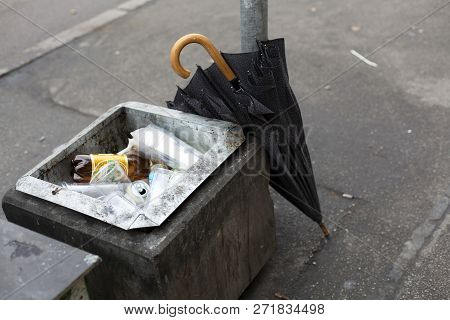 Old Metal Waste Bin On With Broken Umbrella On The Street
