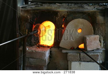 blast furnace for heating glass. this also shows a glass vase being put back in to get reheated before blowing. poster