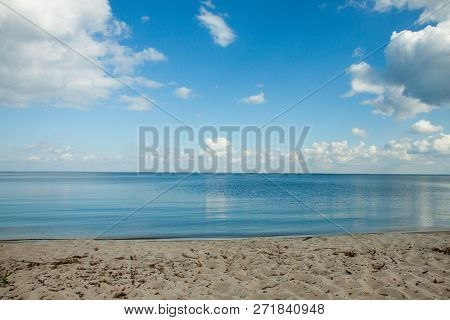 Big Clouds Reflecting On The Smooth Water Surface. Warm Autumn Day Near The Lake Or A Sea. Sandy Sho