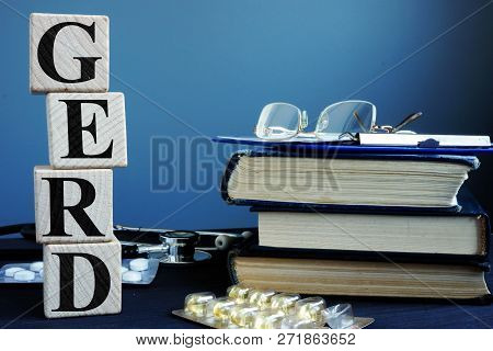 Word GERD Gastroesophageal reflux disease from cubes and book. poster