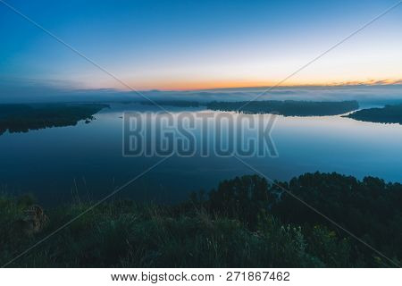 poster of Mystical view from high shore on river. Riverbank with forest under mist. Early haze above trees. Orange glow in picturesque predawn sky. Colorful morning atmospheric calm landscape of majestic nature