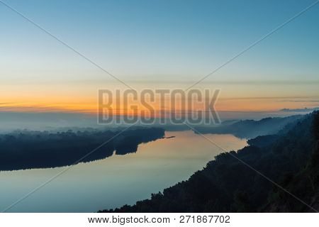 View from high shore on river. Riverbank with forest under thick fog. Dawn reflected in water. Yellow stripe in picturesque predawn sky. Colorful calm morning atmospheric landscape of majestic nature. poster