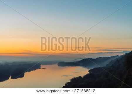 View from high shore on broad river. Riverbank with forest under thick fog. Dawn reflected in water. Yellow glow in picturesque predawn sky. Colorful morning atmospheric landscape of majestic nature. poster