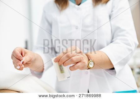 Macro detail of female hand using an insertion tube to insert a Goshin acupuncture needle in the back of a female patient. poster