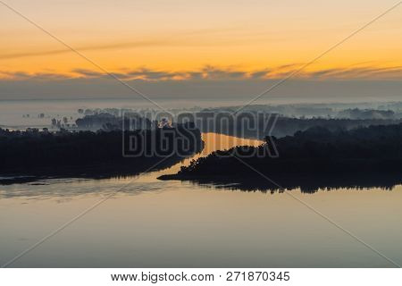 Riverbank with forest under predawn sky. Early blue sky reflected in river water. Yellow stripe in picturesque sky. Fog hid trees on island. Mystical morning atmospheric landscape of majestic nature. poster