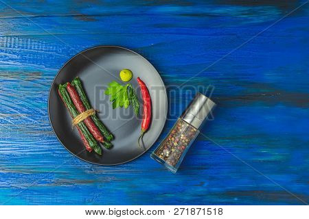 Kabanosy, Sausages Traditional Polish And Green With Wasabi  Made Of Pork In Plate On A Dark Blue Wo