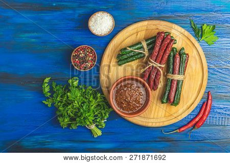 Kabanosy, Sausages Traditional Polish And Green With Wasabi Made Of Pork On Bord On A Dark Blue Wood